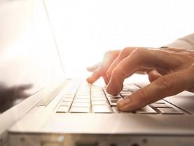 Kädet tietokoneen näppäimistöllä