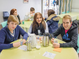 Opiskelijat kahvilla pöydän ääressä
